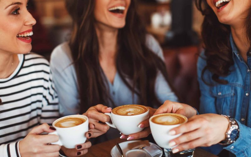 Women holding cups of coffee happily discussing rewards and discounts - Llama Life